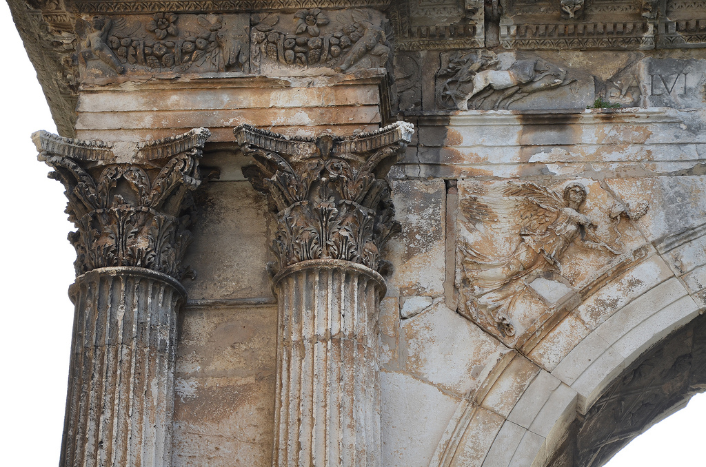 Detail of the Arch of the Sergii. Standing 8 meters high, the arch was constructed in Corinthian style with strong Hellenistic influences. It is richly adorned with relief decorations of grapevines while its centre depicts a scene of an eagle fighting a snake. Two winged victories stand between the inner half columns.