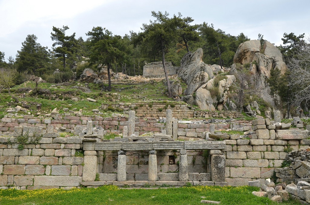 The Well-house with three low gneiss columns with simple Doric marble capitals, note the huge Split Rock in the background which may have been the inspiration for the establishment of the cult to the Carian sky god, Labraunda, Caria, Turkey