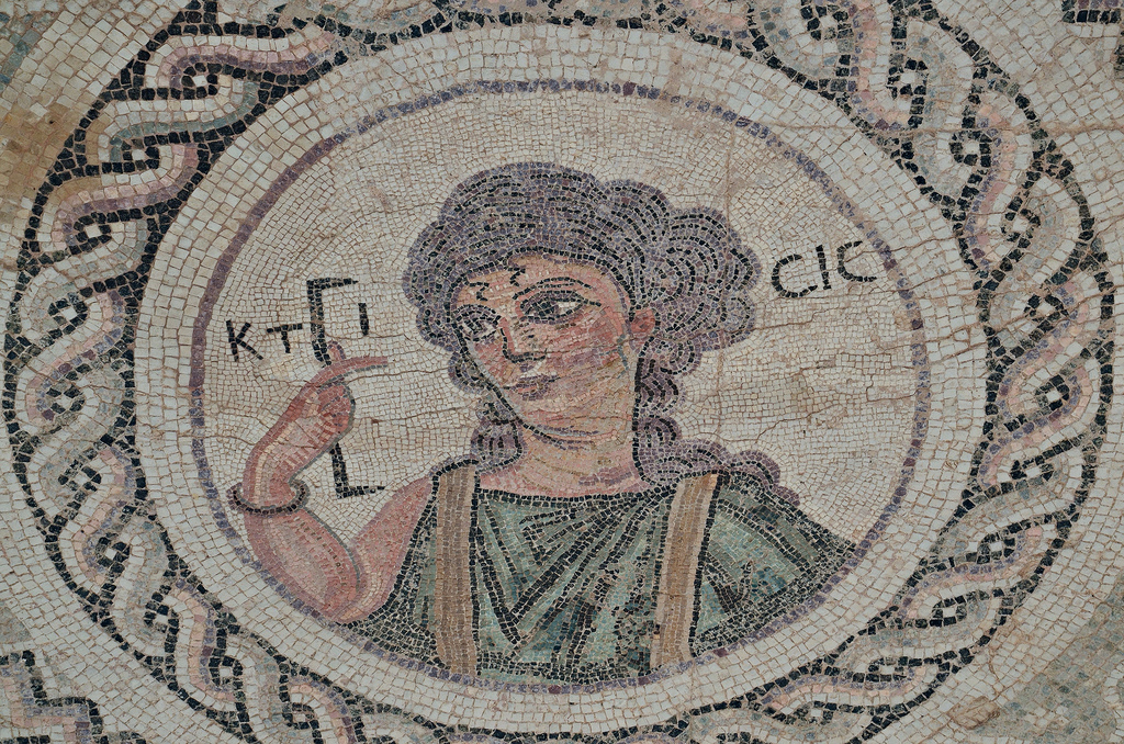 Byzantine mosaic emblema in the House of Eustolios depicting a young woman in a medallion holding a measuring instrument equating of a Roman foot, the Greek inscription identifies her as Ktisis, the personification of Foundation/Donation/Creation, Kourion