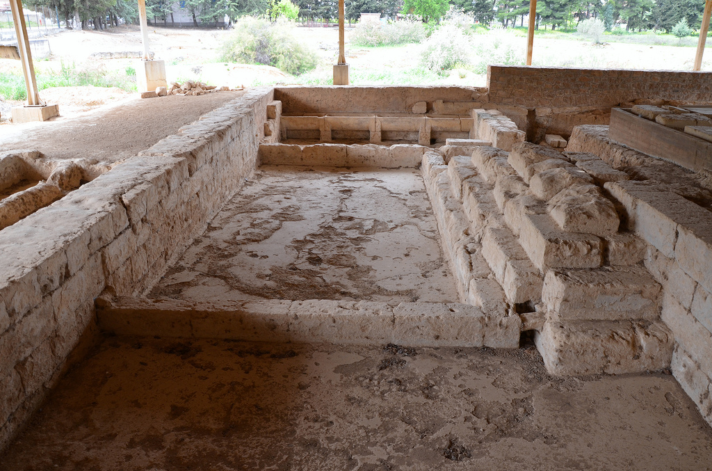 The bath house with a large central pool flanked by two tub rooms, each with four stone wash basins still in situ.