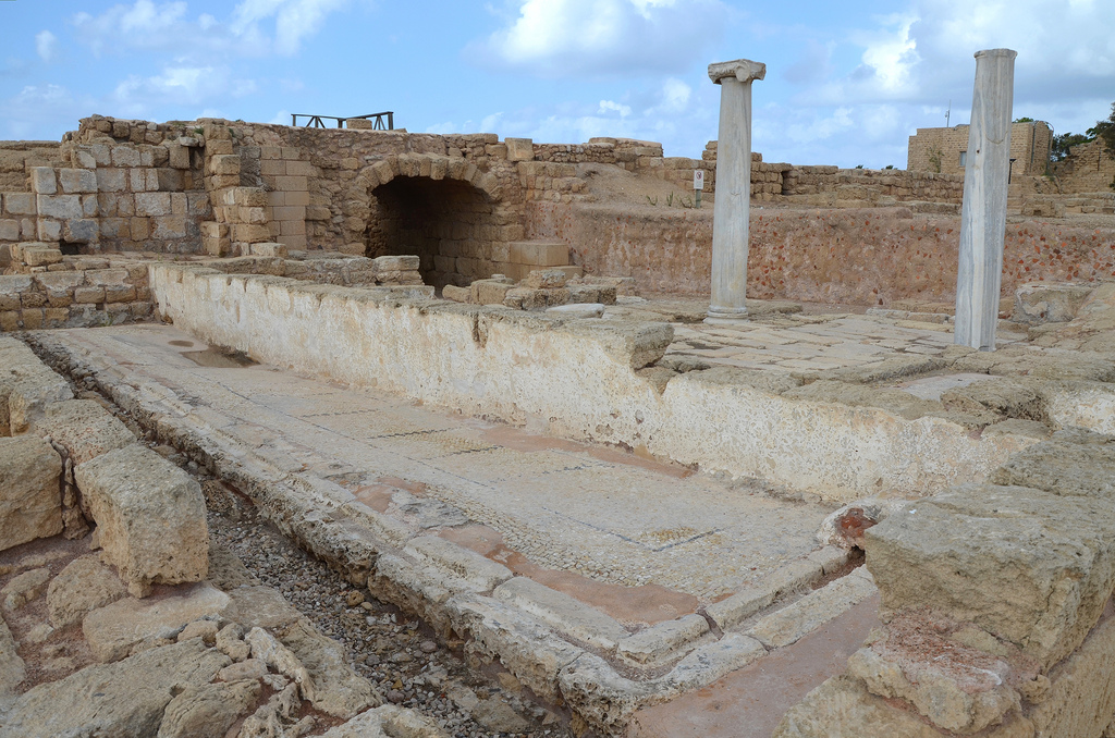 The public latrine used during the Roman and Byzantine periods. Marble benches were set along the southern and western walls of the latrine. Water flushed through its channels laid a the bottom of the walls and connecting with the main sewer beneath the decumanus street.