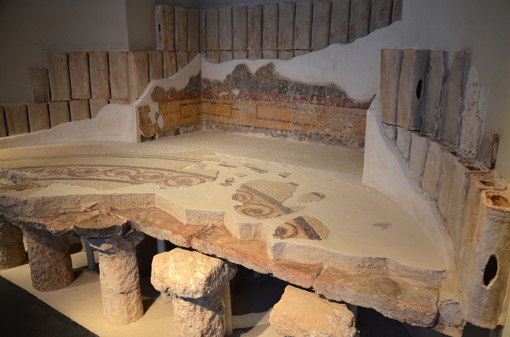 Reconstruction of a part of the round hot room (caldarium) from Herod's bathhouse at Herodium with remains of the frescoes and flues from the walls of the room and a mosaic floor decorated with scrolls, 1st century BC. Israel Museum, Jerusalem.