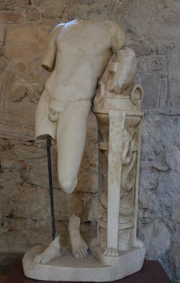 Marble statue of Pythian Apollo leaning on the Delphic tripod encoiled with a serpent and holding Apollo's tortoise shell lyre.