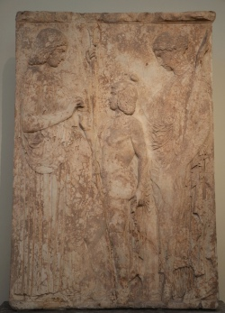 This is the largest and most important votive relief found at Eleusis. It represents the Eleusinian deities in a scene of mysterious rituel. On the left Demeter, clad in a peplos and holding a scepter in her left hand, offers ears of wheat to Triptolemos, son of Eleusinian king Keleos, to bestow on mankind. On the right Persephone, clad in a chiton and mantle and holding a torch, blesses Triptolemos with her right hand. This relief, dating to c. 440-430 BCE, was apparently famous in antiquity and was copied in the Roman period. (Archaeological Museum of Athens, Greece)