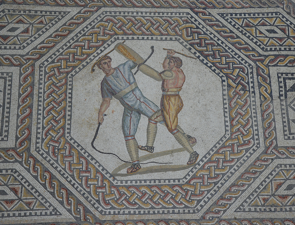 Octagonal medallion depicting two combatants attacking one another with cudgels and a whip. The introduction to the gladiatorial contests consisted of a prolusio (prelude). The various pairs fought with blunted weapons, giving the foretaste of their skills.