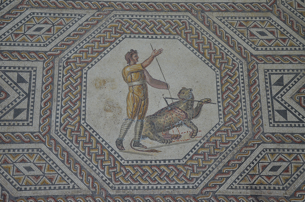 Octagonal medallion depicting a Javelin thrower with a panther. The games usually began with venationes (beast hunts) and bestiarii (beast fighting) gladiators. Here the beast is wounded by the venator's spear and tries to pull the javelin out. It succeeds only in breaking it in half. Delighted with his conquest, the proud venator received the acclamation of the crowd.