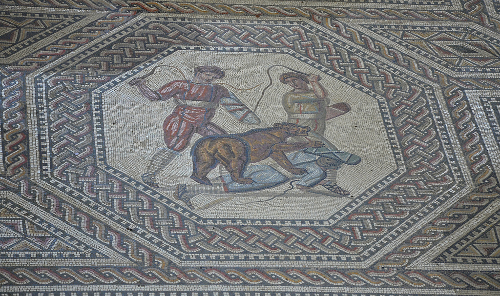 Octagonal medallion depicting two rogues trying to drive the animal off by lashes from their whips. In this panel, which is in the center of the mosaic, a bear has thrown one of his tormentors to the ground, while the other two attempt to drive the animal off by lashes from their whips. The venatores are wearing knee-breeches and very broad belts in addition to the leg wrappings. Later their clothing was reduced to the tunica.