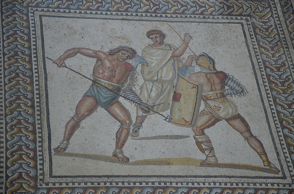 Octagonal medallion depicting a Retiarus armed with trident and dagger fighting against a Secutor while a referee looks on. In the afternoon came the high point of the games, individual gladiatorial combats. These were usually matches between gladiators with different types of armor and fighting styles, supervised by a referee (summa rudis). This scene represents simultaneously the highlight and the conclusion of the games.