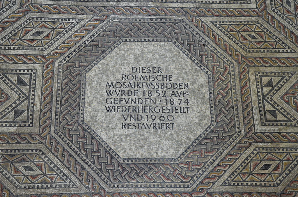 Following restorations in 1960/61 the following text was inserted: This Roman mosaic floor was discovered in 1852, reconstructed in 1874 and restored in 1960. The original medallion has been destroyed, perhaps intentionally, by later occupants of the villa.