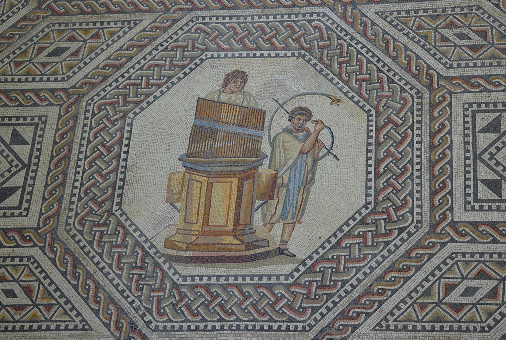 Medallion depicting a organist and horn player. The beginning and the end of the Roman games were often accompanied by music. The mosaicist has depicted the water organ (hydraulis), know in the ancient world since 300 BC. The 27 organ-pipes rest on a hexagonal podium which also serves to store water for the organ. The organist plays the keyboard situated behind the pipes. The curved horn, which is braced and supported on the shoulder of the player by a cross bar, is a cornu.