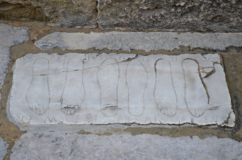 Votive plaque with engraved footprints at the entrance of the Roman amphitheatre.