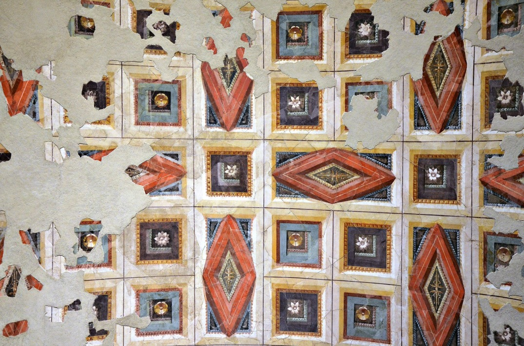 The ceiling is decorated with a painted pattern of rhomboidal and square coffers containing rosettes, whose relief was suggested by the use of shading as well as by means of perspective. The frames were rendered in shades of red, yellow and white, the inner moulding in orange, yellow, blue and green, and ornaments of the coffers in purple, black, white and yellow.