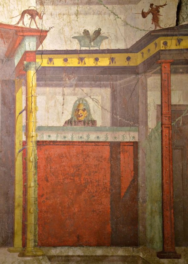 The architecture depicted in the Room of the Masks is a one-storey structure with a central recess and narrow side-doors on each side, probably evoking a scaenae frons, a wooden theatre stage building.