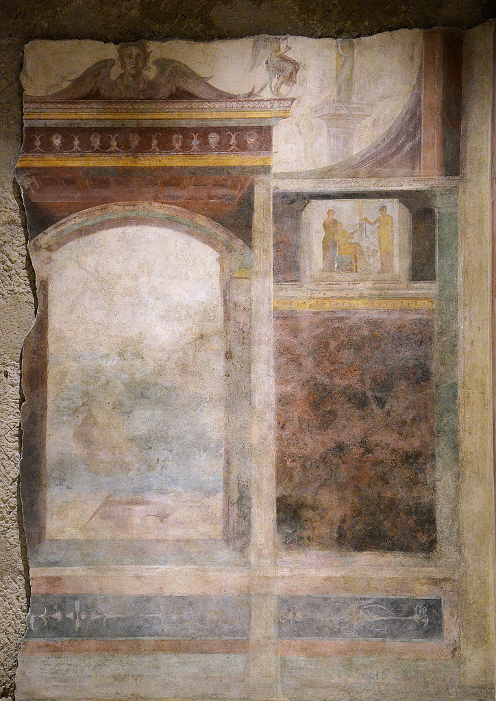 Detail of wall painting on the back wall of the tablinum. Around the central panel (now totally illegible) are backdrops of illusionistic architecture and small panels with ritual scenes.